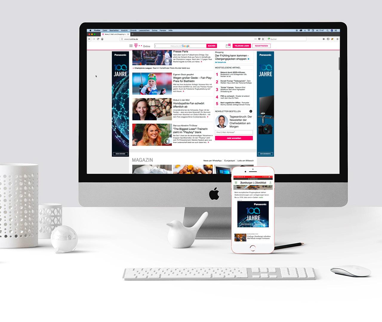 Schreibtisch mit PC Bildschirm, Tastatur und Smartphone in dem eine Panasonic Anzeige abläuft
